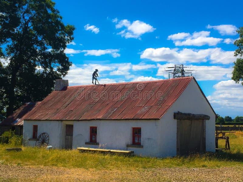 Cabaña irlandesa blanqueada vieja rústica con el fiddler en el tejado imágenes de archivo libres de regalías
