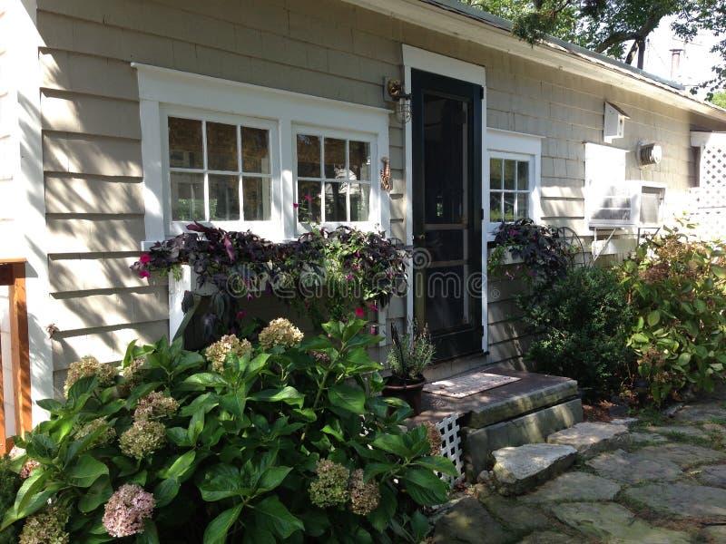 Cabaña pintoresca con las flores imágenes de archivo libres de regalías