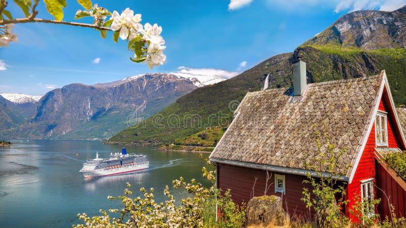 Cabaña roja contra el barco de cruceros en el fiordo, Flam, Noruega