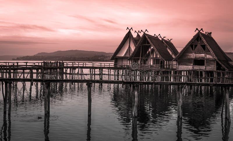 Cabañas cubiertas con paja suspendidas en los zancos sobre el lago foto de archivo