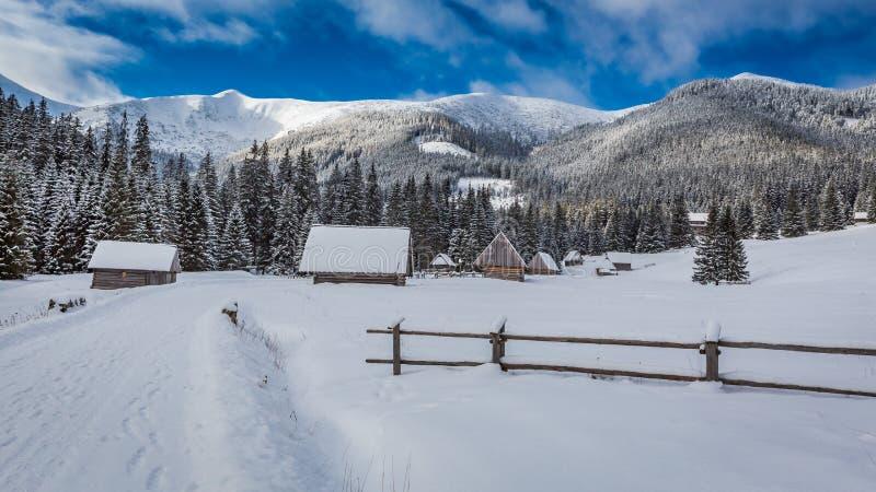 Cabañas cubiertas por la nieve en la salida del sol en invierno, montañas de Tatra foto de archivo