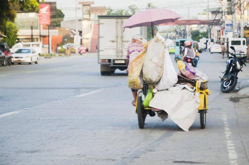 Cabaguio Avenue in Davao, Philippines. With a garbage collector in focus with in trisikad - a human-run vehicle as a means for transport in the Philippines stock photos