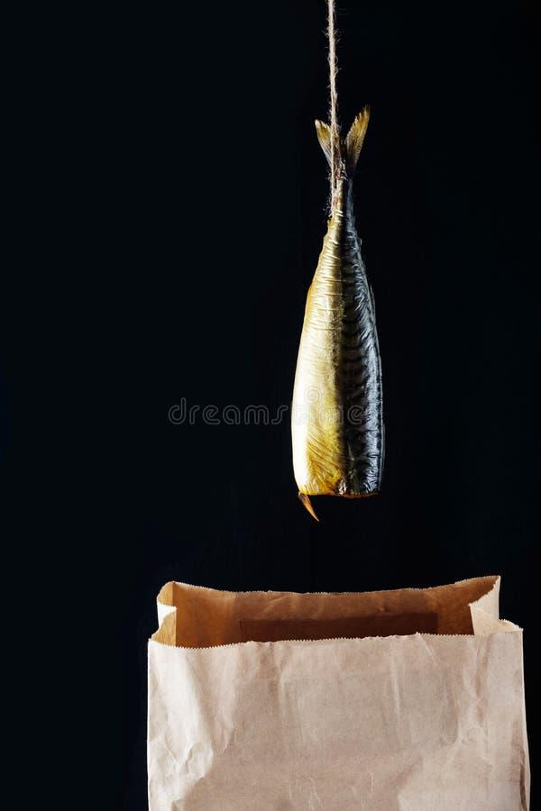 Caballa ahumada de los pescados en la bolsa de papel en el fondo de madera negro foto de archivo libre de regalías