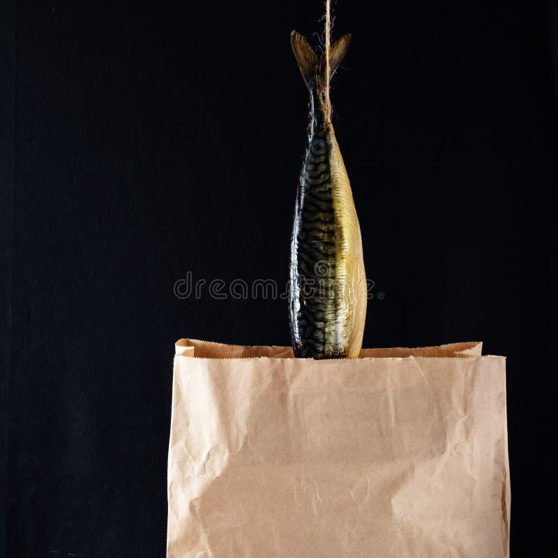 Caballa ahumada de los pescados en la bolsa de papel en el fondo de madera negro imagen de archivo