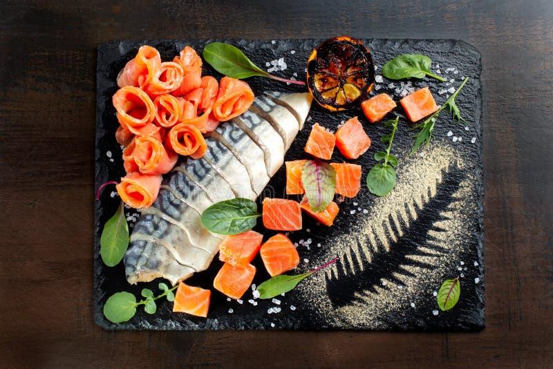 Caballa, pedazos de color salmón Presentado en pizarra negra imagen de archivo