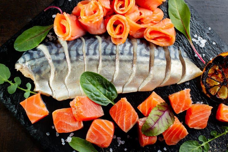 Caballa, pedazos de color salmón Presentado en pizarra negra fotografía de archivo