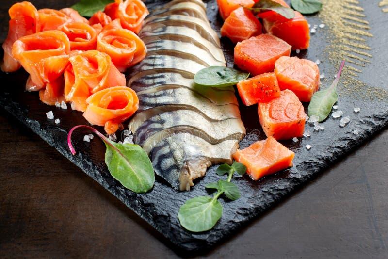 Caballa, pedazos de color salmón Presentado en pizarra negra foto de archivo libre de regalías