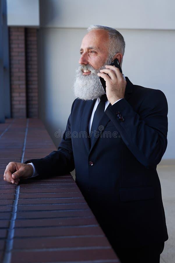 Caballero apuesto que habla en el teléfono mientras que se inclina en travesaño fotos de archivo libres de regalías