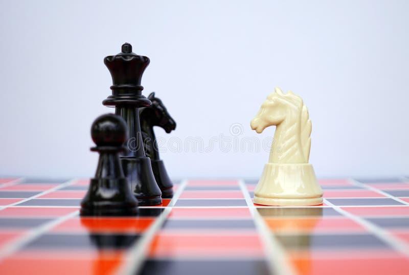 Caballero blanco que hace frente a ajedrez negro foto de archivo libre de regalías