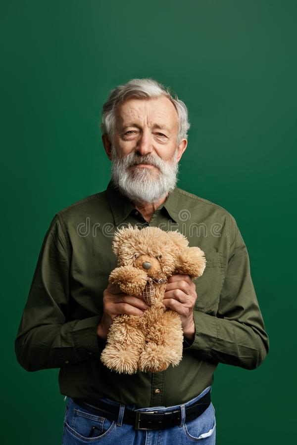 Caballero mayor hermoso dulce que sostiene un oso de peluche aislado en fondo verde fotos de archivo