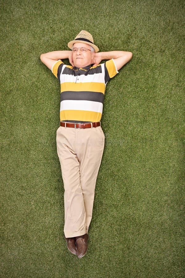 Caballero mayor relajado que miente en hierba en un campo imagen de archivo libre de regalías