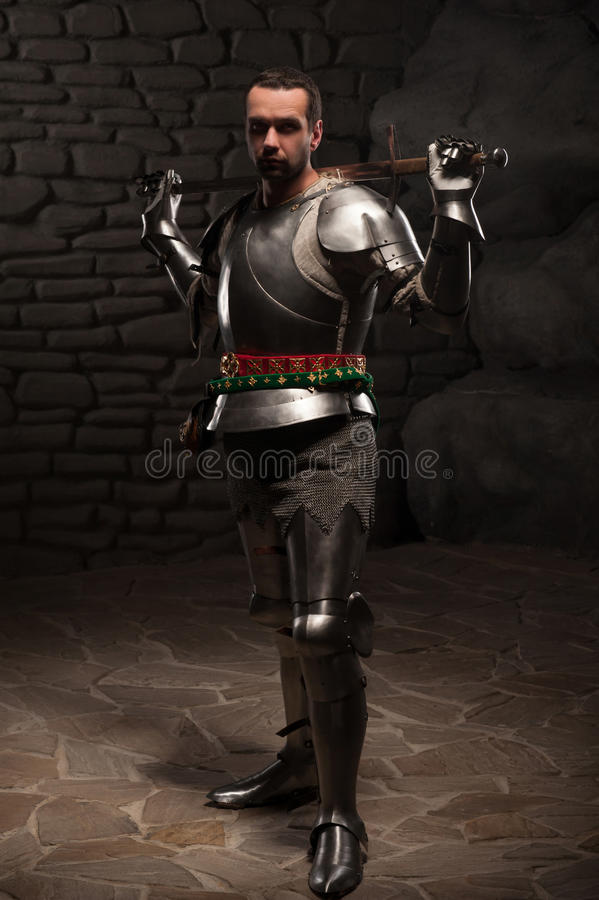 Caballero medieval que presenta con la espada en una piedra oscura imagen de archivo libre de regalías