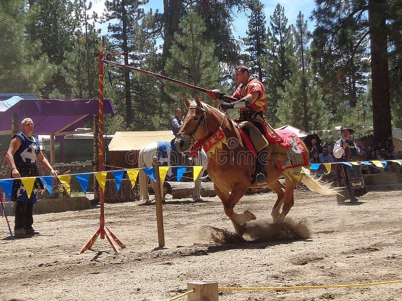 Caballero rojo Catching de Faire del renacimiento de Big Bear el anillo en el torneo de la justa imagen de archivo libre de regalías