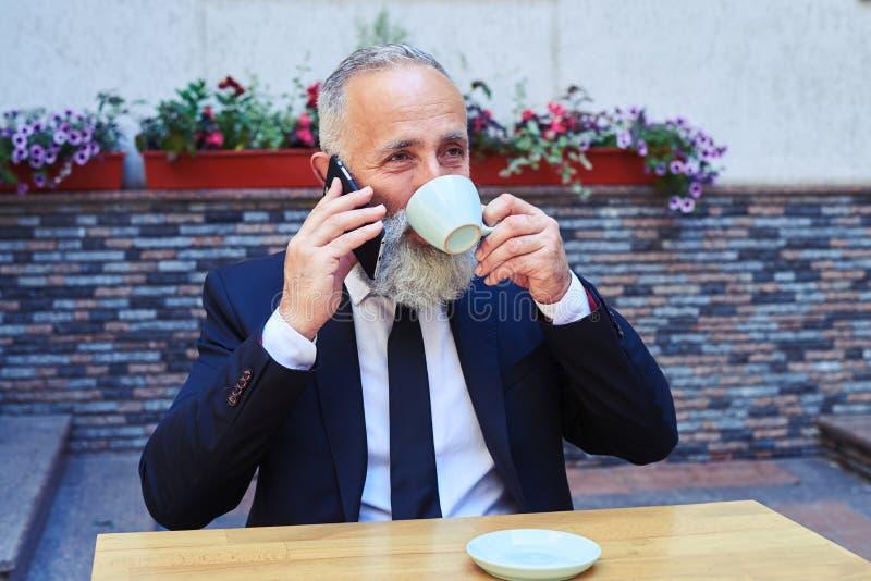 Caballero sonriente que habla en el teléfono mientras que bebe el café imágenes de archivo libres de regalías