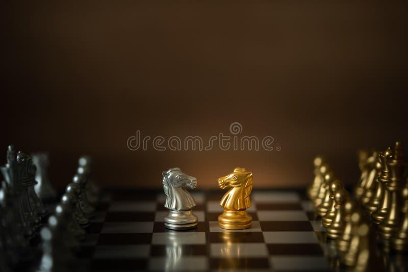 Caballeros dorados y blancos frente al tablero de ajedrez entre el equipo blanco y el negro foto de archivo libre de regalías