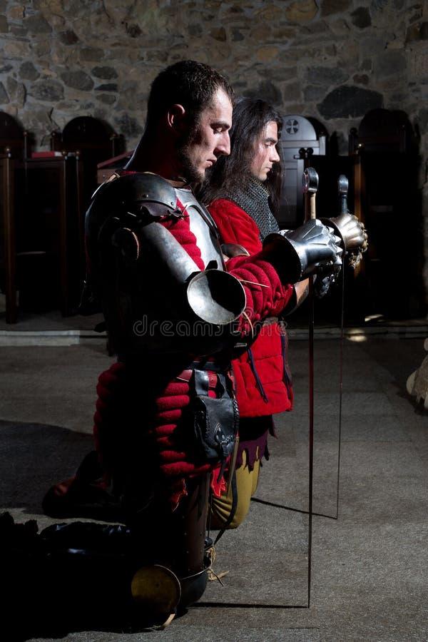 Caballeros valientes que ruegan en la iglesia vieja antes de la batalla fotos de archivo