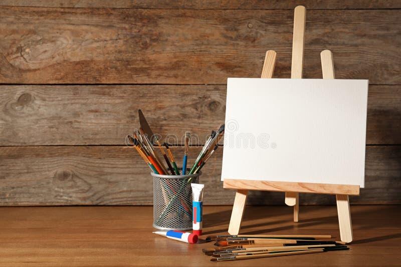 Caballete con el tablero en blanco de la lona y herramientas de pintura para los niños en la tabla cerca de la pared de madera fotografía de archivo libre de regalías