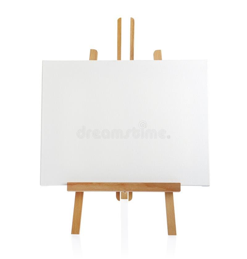 Caballete de madera con la lona en blanco fotografía de archivo