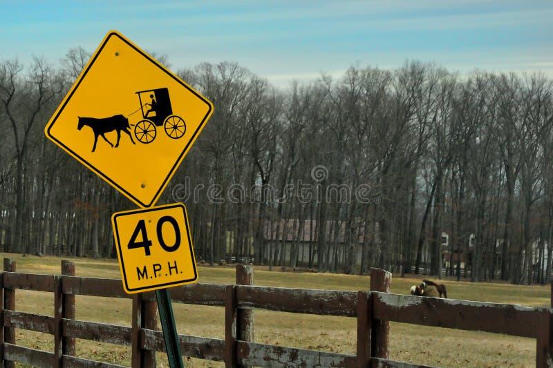 Caballo de Amish y señal de tráfico con errores en primero plano con los caballos que pastan en el fondo imagen de archivo
