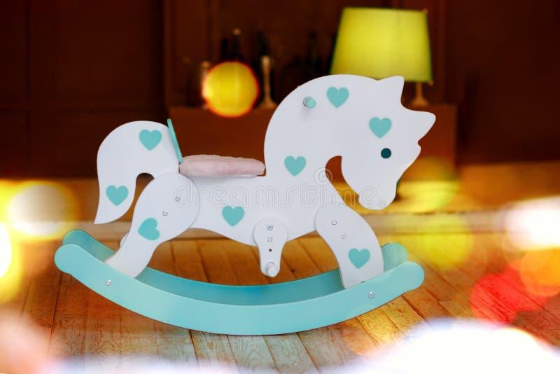 Caballo de juguete con luces de Navidad en fondo de madera imágenes de archivo libres de regalías