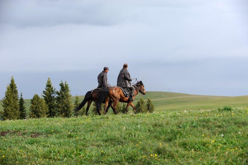 Caballo de montar a caballo chino de los ganaderos del Kazakh en grasslan fotografía de archivo libre de regalías