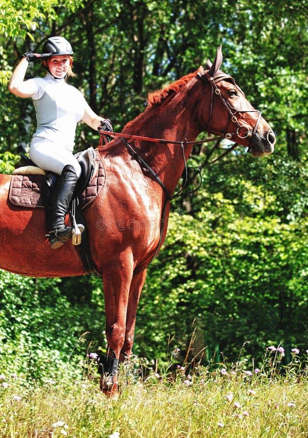 Caballo de montar a caballo de la mujer en país imagen de archivo