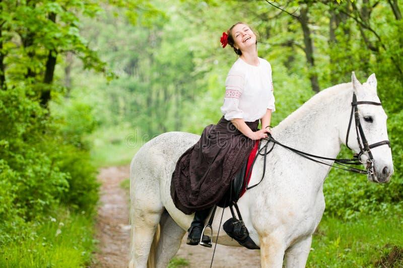 Caballo de montar a caballo de risa de la muchacha fotografía de archivo