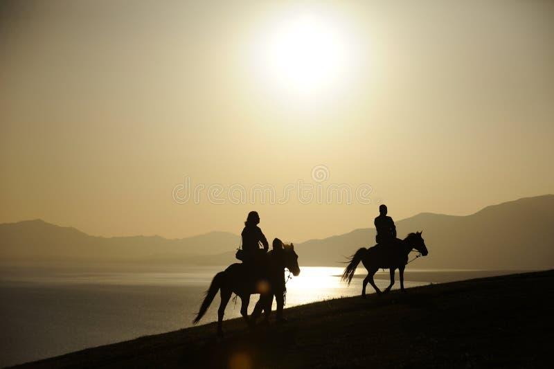 Caballo de montar a caballo en la salida del sol foto de archivo libre de regalías