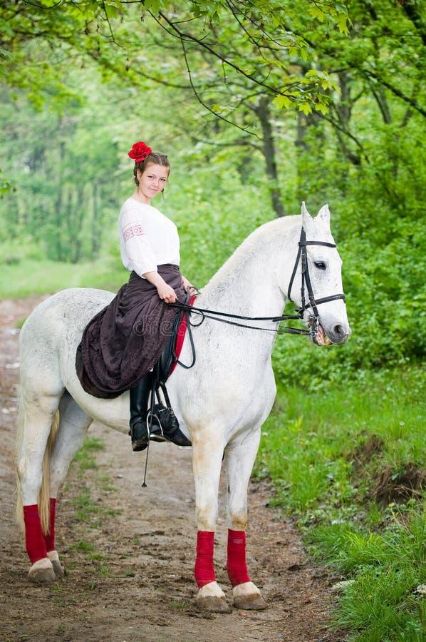 Caballo de montar a caballo hermoso de la muchacha fotografía de archivo