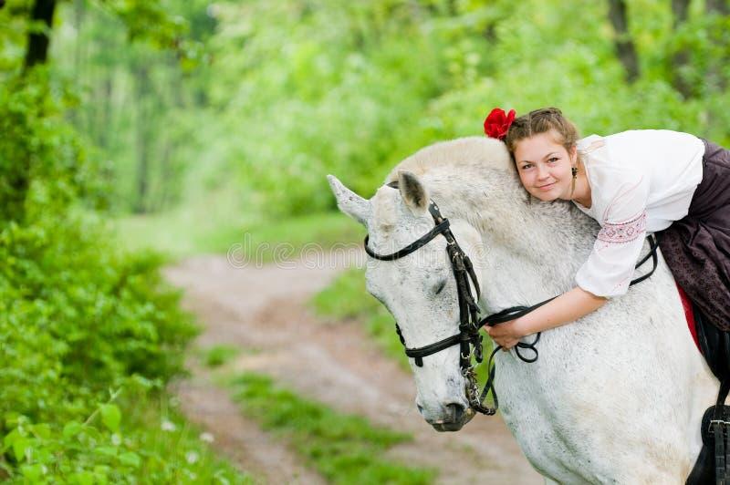 Caballo de montar a caballo lindo de la muchacha foto de archivo libre de regalías
