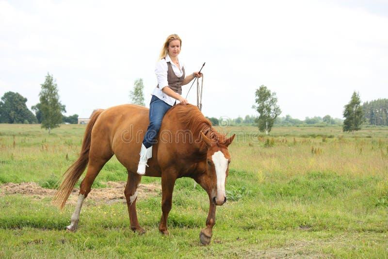 Caballo de montar a caballo rubio hermoso de la mujer a pelo fotos de archivo