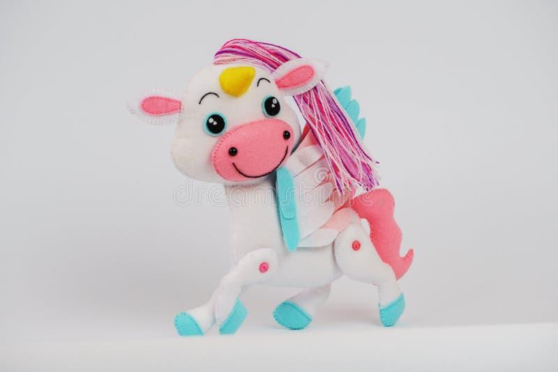 Caballo del juguete de los niños hecho del fieltro en un fondo blanco foto de archivo