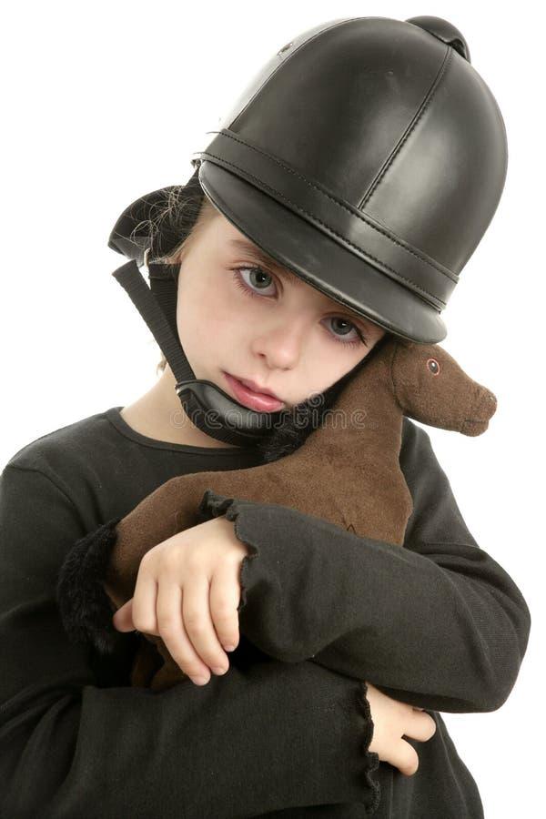 Caballo del juguete del abrazo de la niña del casquillo del montar a caballo fotografía de archivo