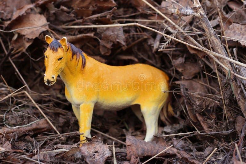 Caballo del juguete en la naturaleza fotografiada como real entre fotos de archivo