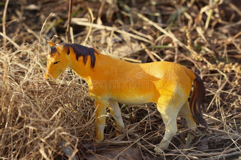 Caballo del juguete fotografiado afuera en hierba seca fotografía de archivo