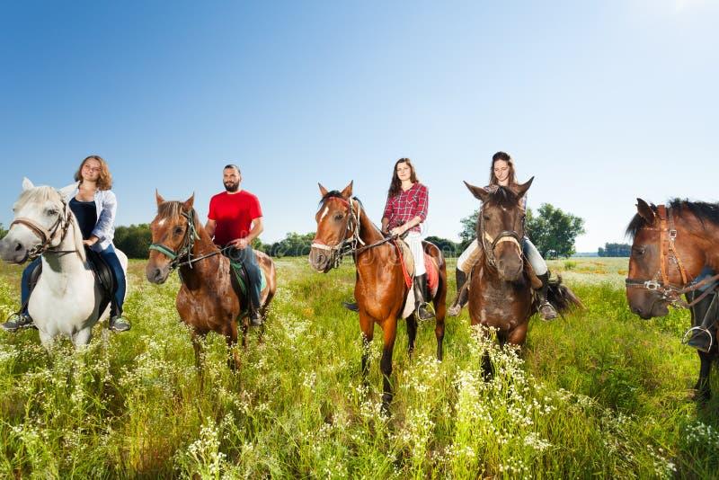 Caballos de montar a caballo felices de los equestrians en campo del verano imagen de archivo libre de regalías