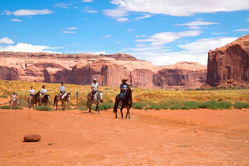 Caballos de montar a caballo de la gente en el desierto imagenes de archivo