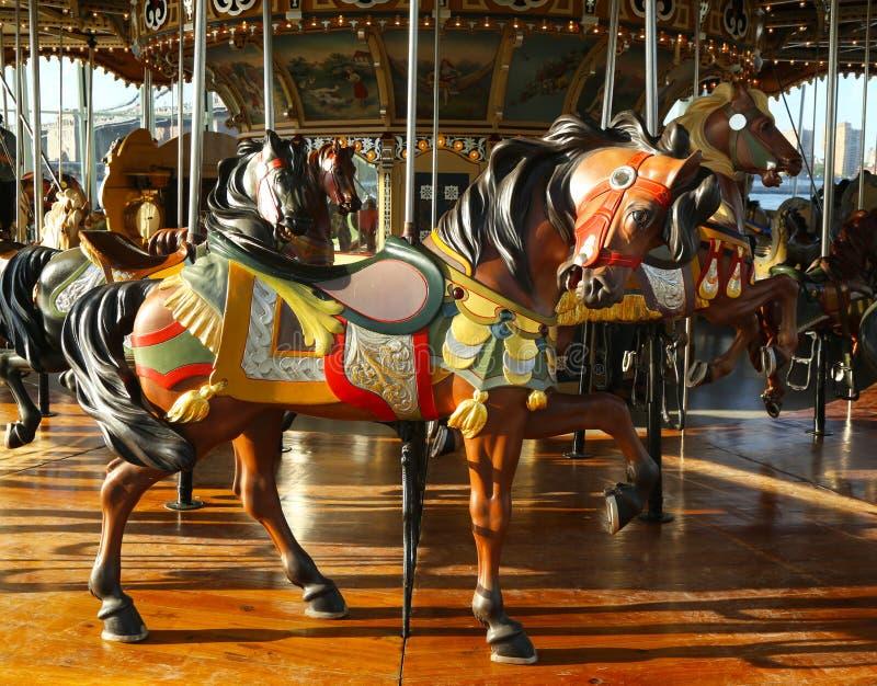 Caballos en un carrusel tradicional del parque de atracciones imagen de archivo
