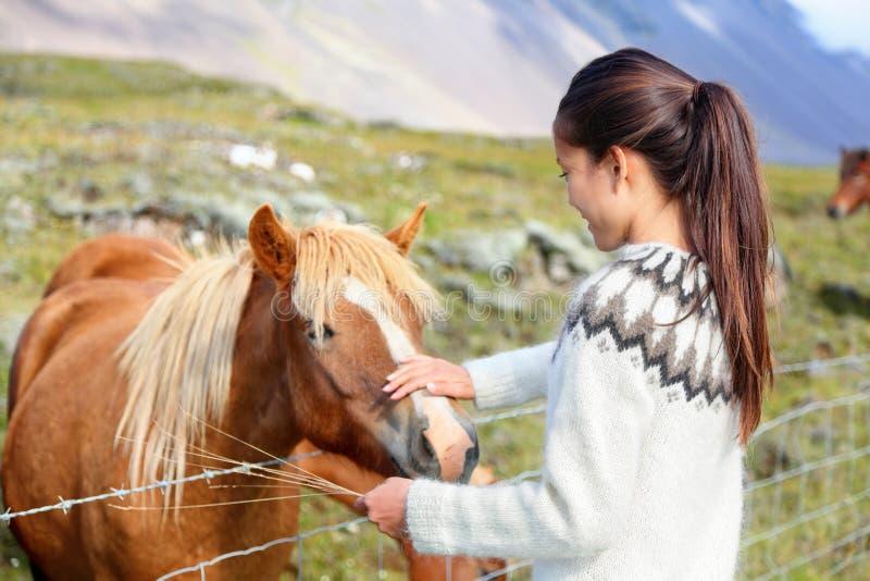 Caballos islandeses - mujer que acaricia el caballo en Islandia foto de archivo