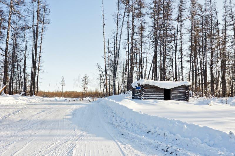 Cabana abandonada do inverno na estrada de floresta do inverno fotografia de stock
