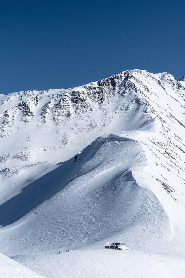 Cabana alpina coberto de neve da montanha com os dois esquiadores no inverno imagens de stock