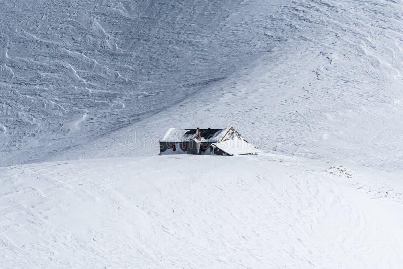 Cabana alpina da montanha isolada no campo de neve windpacked imagens de stock royalty free