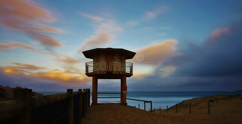 Cabana da salva-vidas na praia contra o por do sol colorido imagens de stock