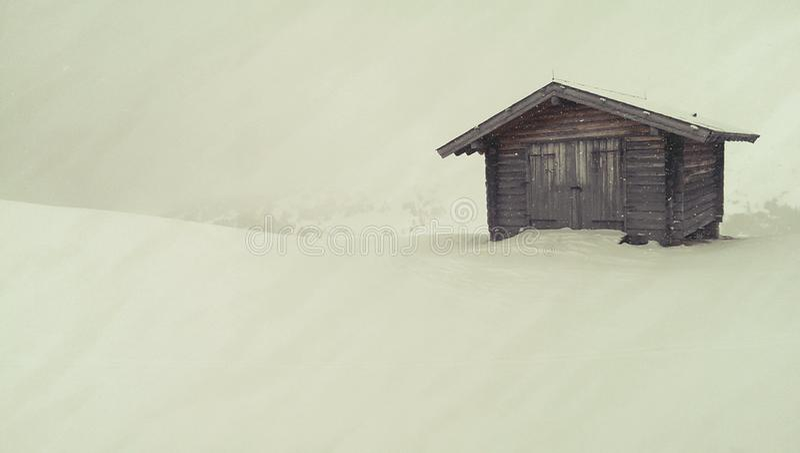 Cabana de madeira em montanhas nevado foto de stock