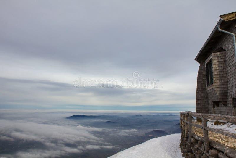 Cabana na montanha que negligencia o vale nevado fotografia de stock