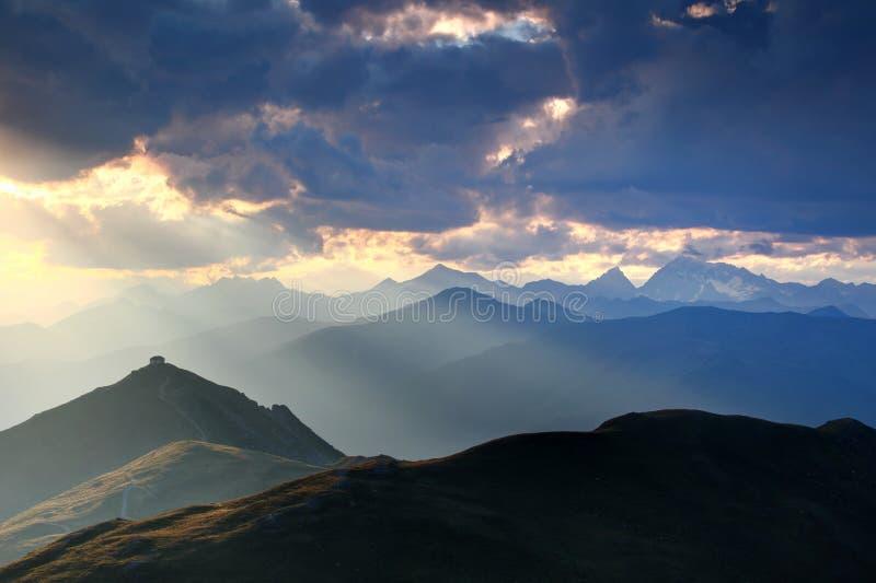 A cabana no auge do pico iluminou-se por raios do sol em cumes Itália de Carnic do por do sol imagem de stock