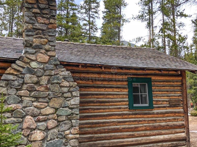 Cabana rústica de madeira rústica da chaminé de pedra no parque nacional imagens de stock