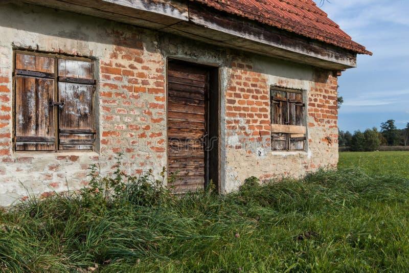 Cabana velha, casa de campo, estável com um prado verde foto de stock