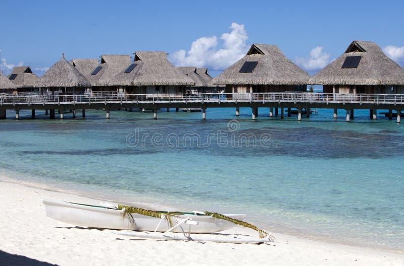 Cabanas na água no mar e em um barco branco pequeno na costa imagens de stock royalty free