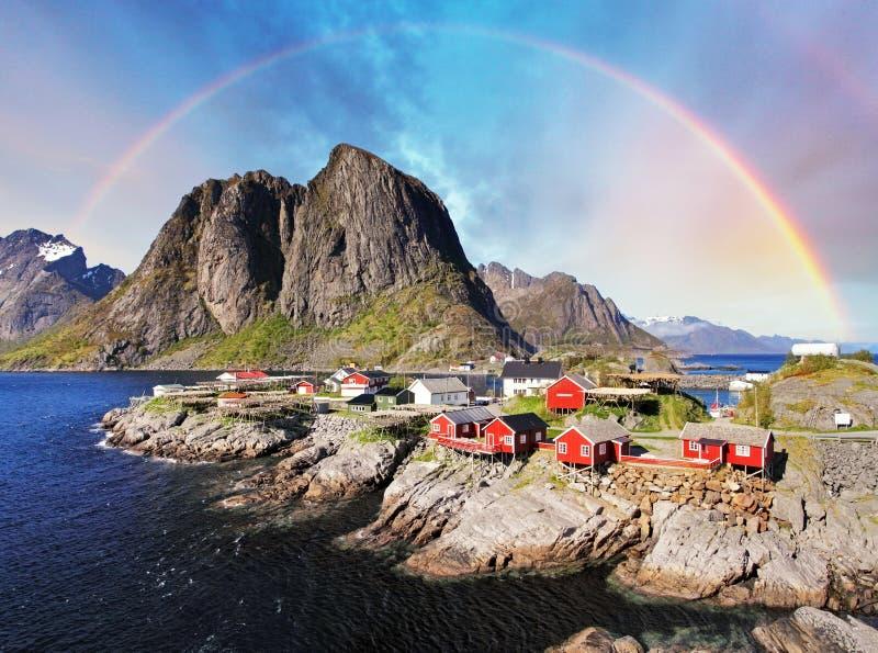 Cabanas norueguesas da aldeia piscatória com arco-íris, Reine, Lofoten Isla imagens de stock